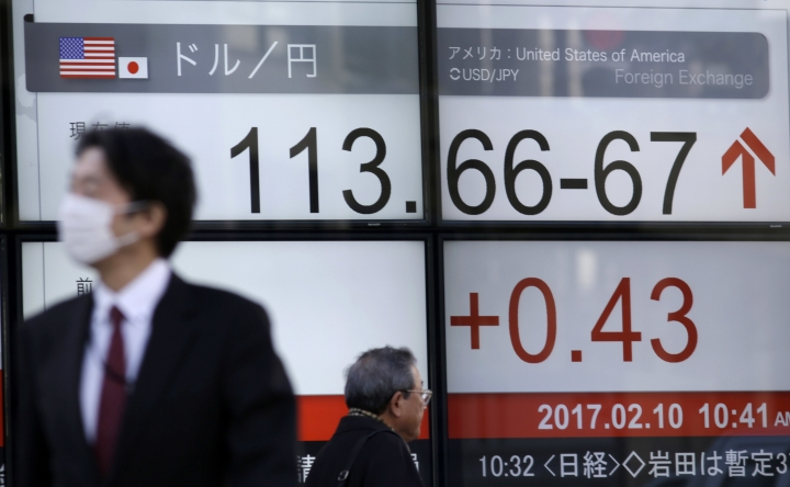 People walk past an electronic stock board showing day's ongoing exchange rate between U.S. dollar and Japanese yen at a securities firm in Tokyo, Friday, Feb. 10, 2017. Asian stocks advanced Friday led by big gains in Japan after U.S. President Donald Trump promised that he would soon cut taxes for businesses. Japan's benchmark Nikkei 225 index surged 2.4 percent as the yen weakened against the dollar, lifting shares of exporters. (AP Photo/Eugene Hoshiko)