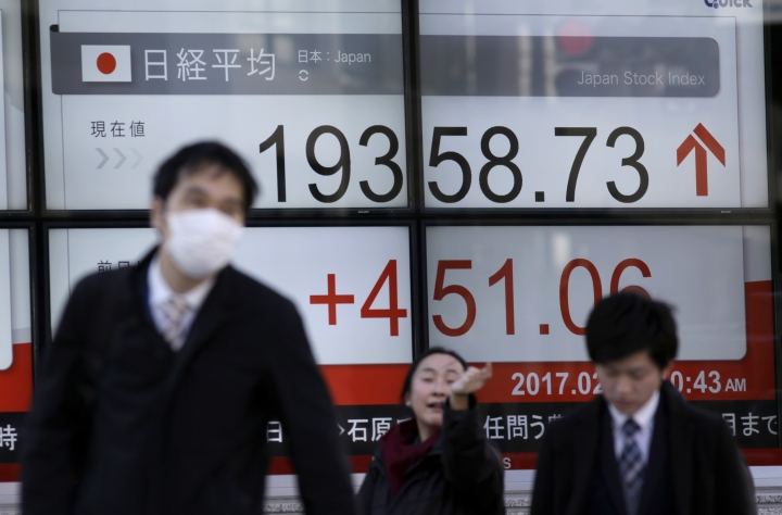 People walk past an electronic stock board showing Japan's Nikkei 225 index at a securities firm in Tokyo, Friday, Feb. 10, 2017. Asian stocks advanced Friday led by big gains in Japan after U.S. President Donald Trump promised that he would soon cut taxes for businesses. Japan's benchmark Nikkei 225 index surged 2.4 percent as the yen weakened against the dollar, lifting shares of exporters. (AP Photo/Eugene Hoshiko)
