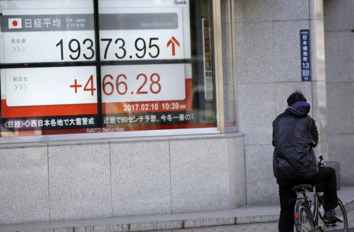 A man looks at an electronic stock board showing Japan's Nikkei 225 index at a securities firm in Tokyo, Friday, Feb. 10, 2017. Asian stocks advanced Friday led by big gains in Japan after U.S. President Donald Trump promised that he would soon cut taxes for businesses. Japan's benchmark Nikkei 225 index surged 2.4 percent as the yen weakened against the dollar, lifting shares of exporters. (AP Photo/Eugene Hoshiko)