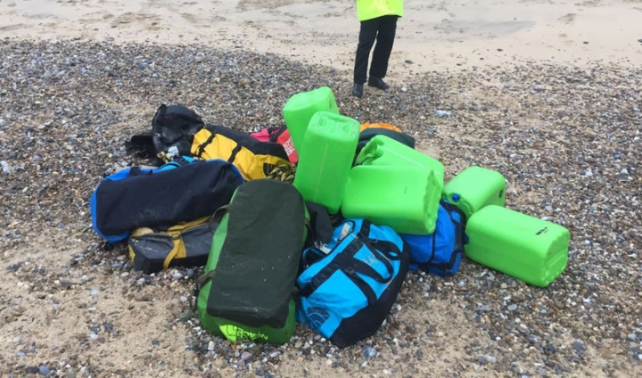 A law enforcement officer stands by holdalls containing cocaine that were washed up on Hopton Beach, near Great Yarmouth, Britain February 9, 2017.  Photograph taken February 9, 2017. National Crime Agency/Handout via Reuters