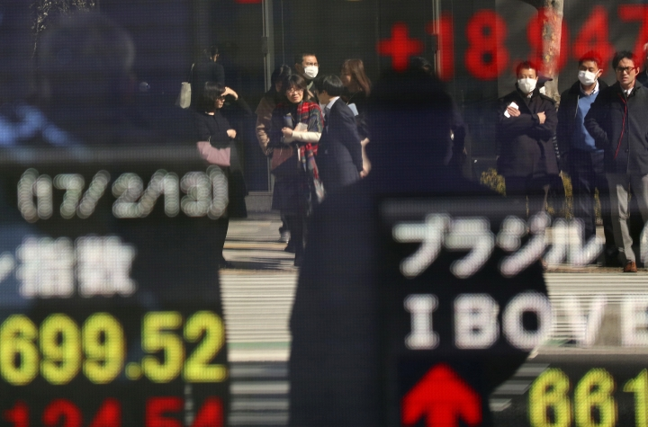 People are reflected on an electronic stock indicator of a securities firm in Tokyo, Monday, Feb. 13, 2017. Asian stock markets have risen after major Wall Street indexes ended last week at record highs and a summit between U.S. President Donald Trump and Japan's Prime Minister Shinzo Abe appeared to sooth tensions over trade and currency policies. Benchmarks in Japan, China, Australia and South Korea all advanced.( (AP Photo/Shizuo Kambayashi)