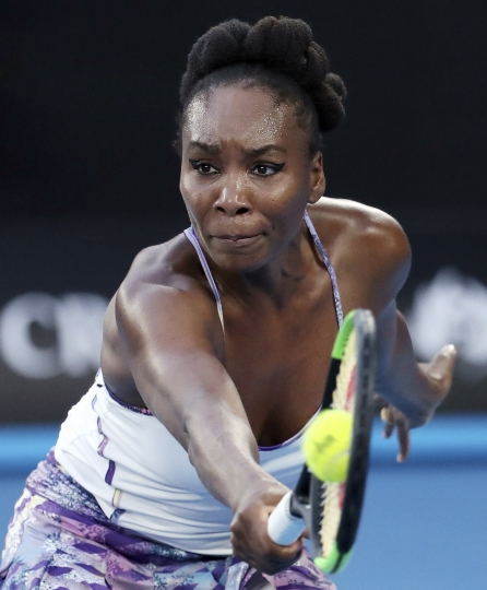 FILE - In this Jan. 28, 2017, file photo, United States' Venus Williams hits a backhand to her sister, Serena, during the women's singles final at the Australian Open tennis championships in Melbourne, Australia. Doug Adler, a tennis commentator dropped by ESPN for a remark about Venus Williams during the Australian Open has sued the network for wrongful termination. Adler, a former tennis pro, maintains he was describing Williams' aggressive style last month as 'guerrilla' tactics and not comparing her with a 'gorilla.' (AP Photo/Aaron Favila, File)