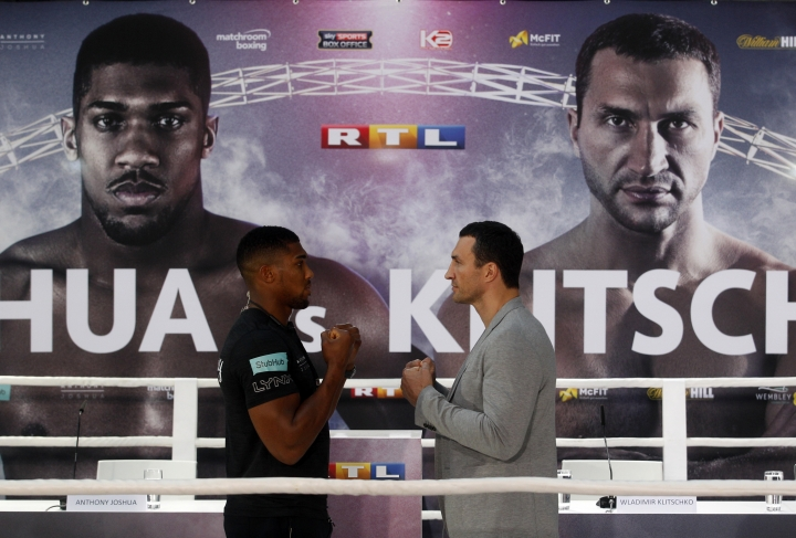 Ukrainian boxer Wladimir Klitschko, right, and Britain's Anthony Joshua face each other during a press conference in Cologne, western Germany, Thursday, Feb. 16, 2017. Klitschko and Joshua will fight for the IBF title in London on April 29. (Roland Weihrauch/dpa via AP)