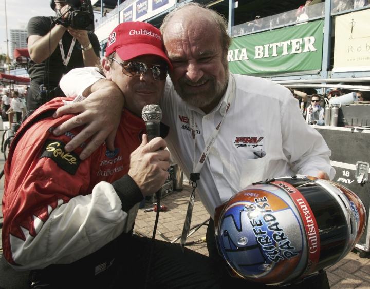 FILE - In this Oct. 23, 2004, file photo, PKV Champ Car racing team owner Kevin Kalkhoven, right, embraces his U.S. driver Jimmy Vasser after receiving a special drivers helmut from Vasser after qualifying at the Lexmark Indy 300, on Australia's Gold Coast. Former CART champion Jimmy Vasser has shut down his IndyCar team after 14 years and seven victories, including the 2013 Indianapolis 500. KV Racing Technology, owned by Australian businessman Kevin Kalkhoven and Vasser, announced the long-rumored move Thursday, Feb. 16, 2017. (AP Photo/Mark Baker, File)