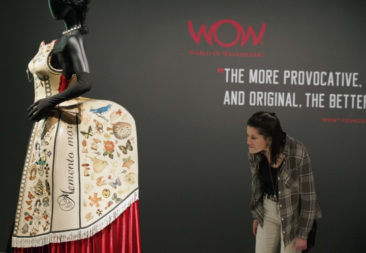 "In this Thursday, Feb. 16, 2017 photo, a woman examines a piece entitled ""Lady Curiosity"" by Fifi Colston, which is part of The ""WOW - World of Wearable Art"" show at the Peabody Essex Museum in Salem, Mass. (AP Photo/Michael Dwyer)"