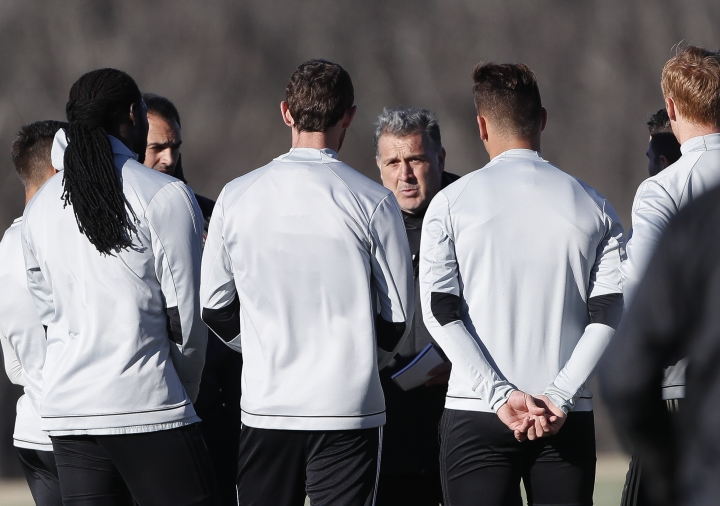 """Atlanta United FC head coach Gerardo """"Tata"""" Martino talks with his players during a soccer training session Thursday, Feb. 16, 2017 in Flowery Branch, Ga. Martino isn't backing down from the high expectations that go with being the MLS expansion Atlanta United coach. As the former coach of the Argentina and Paraguay national teams, Martino knows more than a little about trying to satisfy a demanding fan base. (AP Photo/John Bazemore)"""