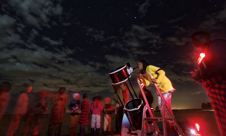 In this photo taken Friday, Feb. 3, 2017, a student looks up at the moon through a telescope, during a visit by The Traveling Telescope to show students the science of astronomy, at St Andrew's School near Molo in Kenya's Rift Valley. Although Kenya lies on the equator and has dramatic nighttime skies in rural areas, children find it hard to name planets and other bodies as astronomy is rarely taught in schools - but that is changing as The Traveling Telescope visits some of the country's most remote areas with telescopes and virtual reality goggles. (AP Photo/Ben Curtis)