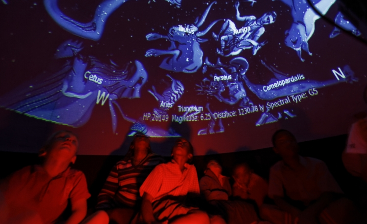 In this photo taken Friday, Feb. 3, 2017, students look up at a projected display inside an inflatable planetarium, during a visit by The Traveling Telescope to show students the science of astronomy, at St Andrew's School near Molo in Kenya's Rift Valley. Although Kenya lies on the equator and has dramatic nighttime skies in rural areas, children find it hard to name planets and other bodies as astronomy is rarely taught in schools - but that is changing as The Traveling Telescope visits some of the country's most remote areas with telescopes and virtual reality goggles. (AP Photo/Ben Curtis)