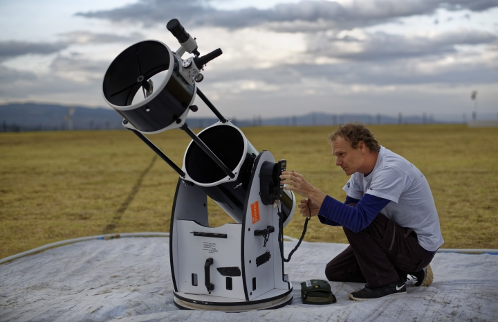 In this photo taken Friday, Feb. 3, 2017, astronomer and company co-founder Daniel Chu Owen sets up a telescope during a visit by The Traveling Telescope to show students the science of astronomy, at St Andrew's School near Molo in Kenya's Rift Valley. Although Kenya lies on the equator and has dramatic nighttime skies in rural areas, children find it hard to name planets and other bodies as astronomy is rarely taught in schools - but that is changing as The Traveling Telescope visits some of the country's most remote areas with telescopes and virtual reality goggles. (AP Photo/Ben Curtis)