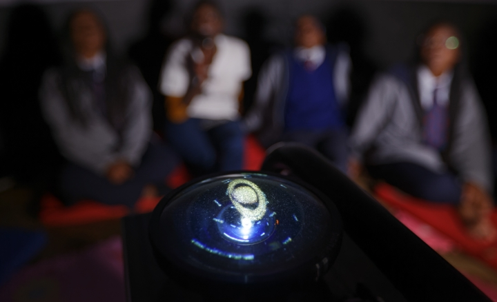 In this photo taken Friday, Feb. 3, 2017, an image of the planet Saturn is seen on the lens of the projector inside an inflatable planetarium, during a visit by The Traveling Telescope to show students the science of astronomy, at St Andrew's School near Molo in Kenya's Rift Valley. Although Kenya lies on the equator and has dramatic nighttime skies in rural areas, children find it hard to name planets and other bodies as astronomy is rarely taught in schools - but that is changing as The Traveling Telescope visits some of the country's most remote areas with telescopes and virtual reality goggles. (AP Photo/Ben Curtis)