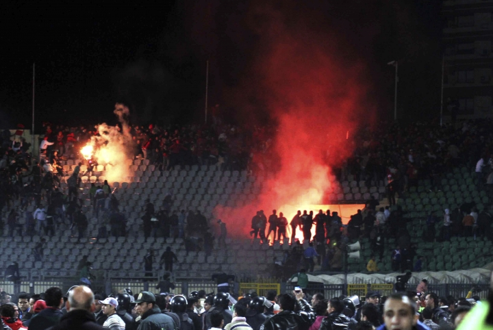 FILE - In this Feb. 1, 2012 file photo, Egyptian fans rush onto the field and clash in the stands following an Al-Ahly club soccer match against Al-Masry club at the soccer stadium in Port Said, Egypt. On Monday, Feb. 20, 2017, Egypt's highest appeals court upheld the death sentences against 10 people convicted over a soccer riot in 2012 that killed over 70 fans, becoming one of the world's deadliest soccer disasters. The verdict by the Court of Cassation is final. The defendants were charged with murder along with several other charges. Also, the court also upheld the convictions of 22 suspects who received up to 10 years in prison over the rioting. (AP Photo, File)