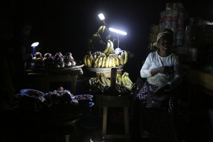In this photo taken on Monday Feb. 20, 2017, vegetable vendors ply their wares by the light of locally-made lanterns in Lagos, Nigeria. In Nigeria, for the cost of powering a small generator for two hours, Dutch company Lumos offer enough solar power to light a house, cool a room with a fan and charge cell phones for about eight hours. For a country without a secure supply of electricity where people are dependent on candles, batteries, kerosene and fuel for generators, Lumos was surprised they spend more on power than solar options. (AP Photo/Sunday Alamba)