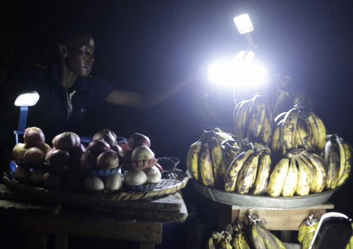 In this photo taken on Monday Feb. 20, 2017, Esther Peter, a plantain and onion vendor, plies her wares by lantern light in Lagos, Nigeria. In Nigeria, for the cost of powering a small generator for two hours, Dutch company Lumos offer enough solar power to light a house, cool a room with a fan and charge cell phones for about eight hours. For a country without a secure supply of electricity where people are dependent on candles, batteries, kerosene and fuel for generators, Lumos was surprised they spend more on power than solar options. (AP Photo/Sunday Alamba)