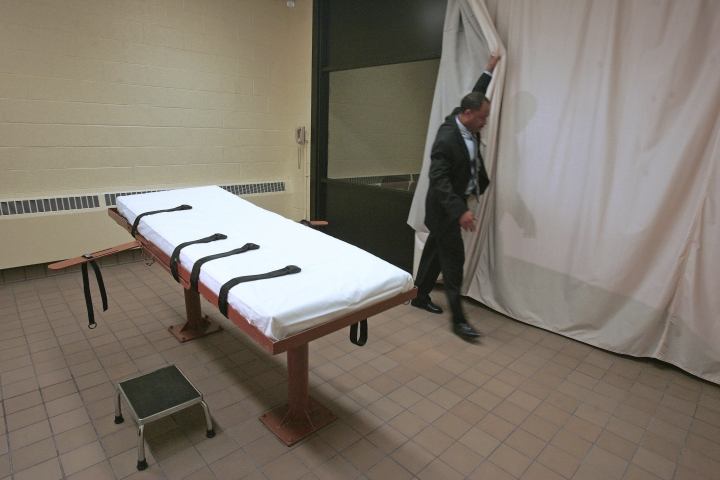 FILE – In this November 2005 file photo, Larry Greene, public information director of the Southern Ohio Correctional Facility, demonstrates how a curtain is pulled between the death chamber and witness room at the prison in Lucasville, Ohio. Legal arguments over the constitutionality of Ohio's lethal injection process, and specifically the effectiveness of the sedative midazolam, are set to be heard by the 6th U.S. Circuit Court of Appeals on Tuesday, Feb. 21, 2017, in Cincinnati, months before the state hopes to start carrying out executions again. (AP Photo/Kiichiro Sato, File)
