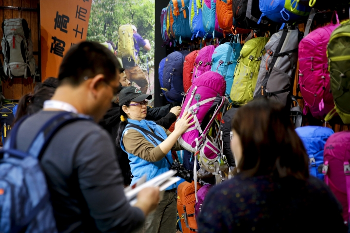 """In this Thursday, Feb. 16, 2017 photo, visitors look at Chinese brand outdoor backpacks on display at the International Trade Show for Mountain and Winter Technologies in Beijing. Chinese Premier Li Keqiang, China's No. 2 leader, expressed hope that disputes with U.S. President Donald Trump's government can be settled amicably and warned a """"trade war would benefit nobody."""" (AP Photo/Andy Wong)"""