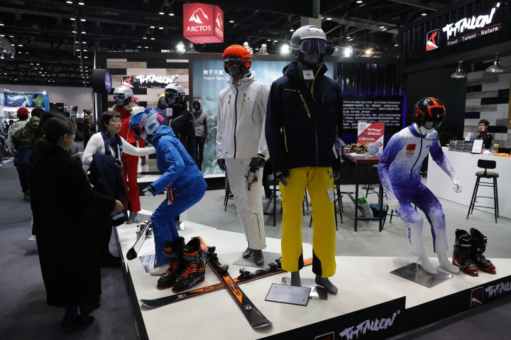 """In this Thursday, Feb. 16, 2017 photo, visitors look at Chinese brand outdoor winter sportswear on display at the International Trade Show for Mountain and Winter Technologies in Beijing. Chinese Premier Li Keqiang, China's No. 2 leader, expressed hope that disputes with U.S. President Donald Trump's government can be settled amicably and warned a """"trade war would benefit nobody."""" (AP Photo/Andy Wong)"""
