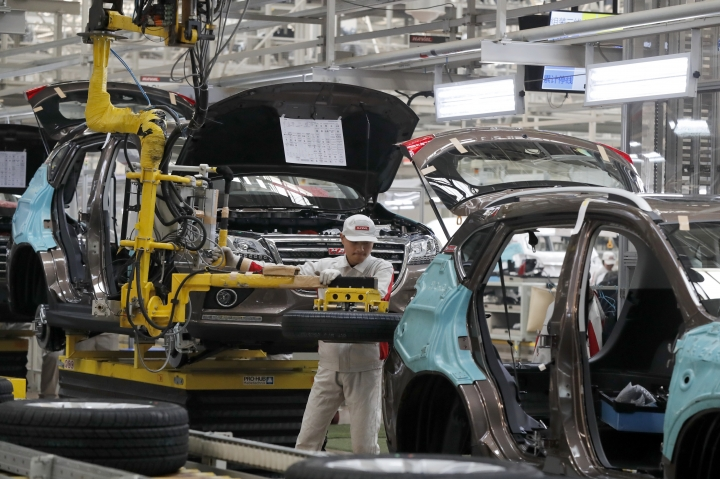 In this Sunday, Feb. 19, 2017 photo, a worker prepares to put a spare tire into a Haval SUV H2 model in the Great Wall Motors assembly plant in Baoding in north China's Hebei province. Great Wall Motors became China's most profitable automaker by making almost nothing but low-priced SUVs. Now it wants to expand into global markets. (AP Photo/Andy Wong)
