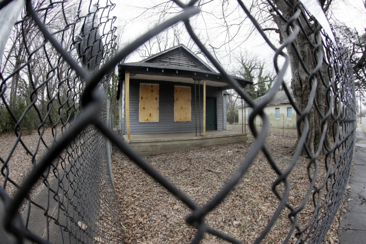 In this Jan. 16, 2017 photo, the abandoned childhood home of singer Aretha Franklin sits behind a security fence in Memphis, Tenn. Officials in charge of fixing up the home say they are working with the DIY Network to move the crumbling structure to a safer location and make it more attractive for visitors. The boarded-up house sits in a blighted neighborhood filled with abandoned homes. A judge had ordered it demolished, but he put that order on hold after preservationists stabilized the house. (AP Photo/Mark Humphrey)
