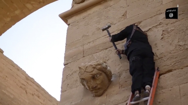 FILE - In this file image made from a militant video posted on YouTube on Friday, April 3, 2015, which has been verified and is consistent with other AP reporting, a militant hammers away at a face on a wall in Hatra, a large fortified city recognized as a UNESCO World Heritage site, 110 kilometers (68 miles) southwest of Mosul, Iraq. At a two-day UNESCO conference, Iraqi officials are asking for money and expertise to reclaim the cultural heritage that is on the verge of complete destruction by the Islamic State group. (AP Photo/Militant video, File)