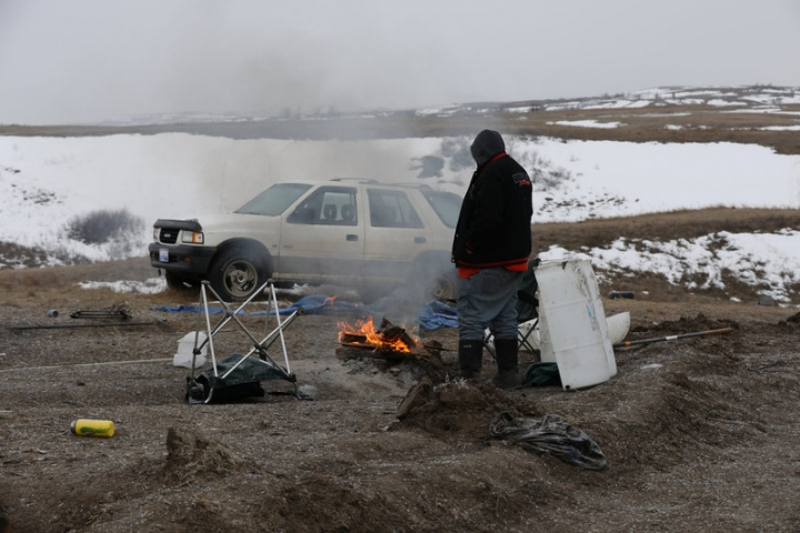 A man warms up by a fire in Sacred Stone camp, one of the few remaining camps protesting the Dakota Access Pipeline in Cannon Ball, North Dakota, U.S., February 24, 2017. REUTERS/Stephen Yang