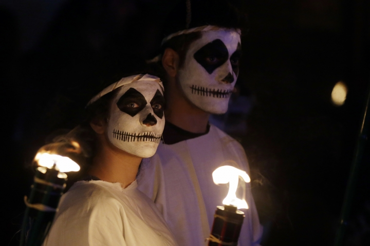 In this photo taken on Saturday, Feb. 25, 2017 a couple watches the Torch Parade on the Greek island of Naxos. Almost 2,000 people took part in the procession of young men and women with faces painted to resemble black-and-white masks wear white sheets and hold torches on long poles. (AP Photo/Thanassis Stavrakis)