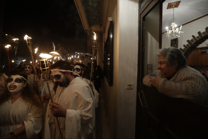 In this photo taken on Saturday, Feb. 25, 2017 an elderly woman watches from her house as the Torch Parade passes by on the Greek island of Naxos. Almost 2,000 people took part in the procession of young men and women with faces painted to resemble black-and-white masks wear white sheets and hold torches on long poles. (AP Photo/Thanassis Stavrakis)