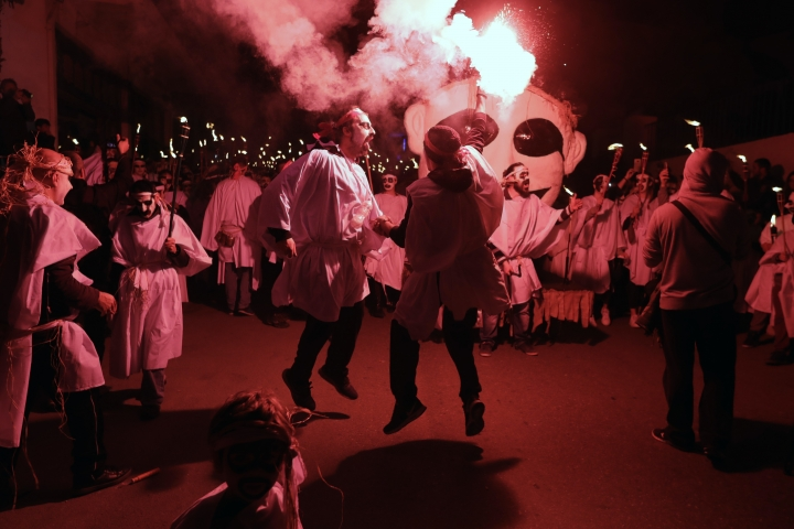 In this photo taken on Saturday, Feb. 25, 2017 two men sing and dance during the Torch Parade on the Greek island of Naxos. Almost 2,000 people took part in the procession of young men and women with faces painted to resemble black-and-white masks wear white sheets and hold torches on long poles. (AP Photo/Thanassis Stavrakis)