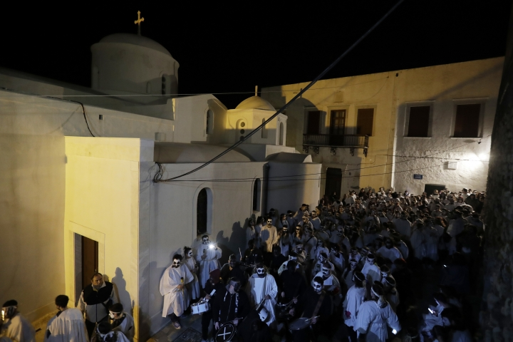 In this photo taken on Saturday, Feb. 25, 2017people gather before the Torch Parade on the Greek island of Naxos. Almost 2,000 people took part in the procession of young men and women with faces painted to resemble black-and-white masks wear white sheets and hold torches on long poles. (AP Photo/Thanassis Stavrakis)