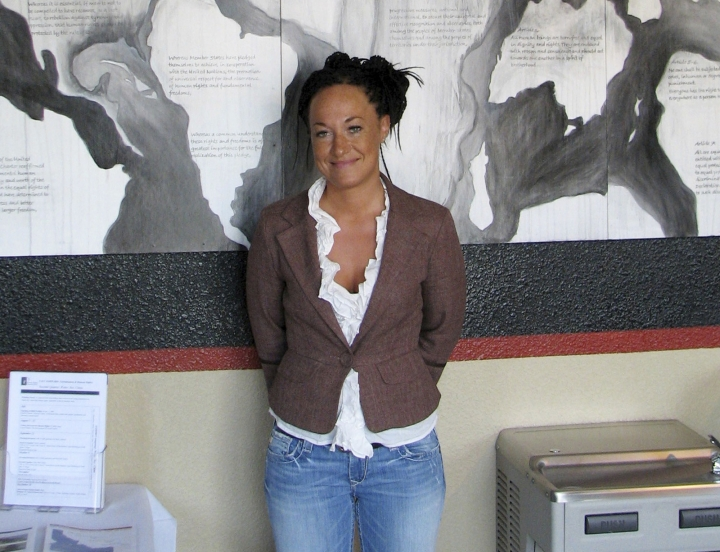 FILE - In this July 24, 2009, file photo, Rachel Dolezal, a leader of the Human Rights Education Institute, stands in front of a mural she painted at the institute's offices in Coeur d'Alene, Idaho. Dolezal tells Britain's The Guardian newspaper for a story published online Feb. 25, 2017, that she can't find a job and she is near homelessness. Dolezal stepped down from her post as the leader of the Spokane, Washington, chapter of the NAACP in 2015 amid criticism that she was passing herself off as black. (AP Photo/Nicholas K. Geranios, File)
