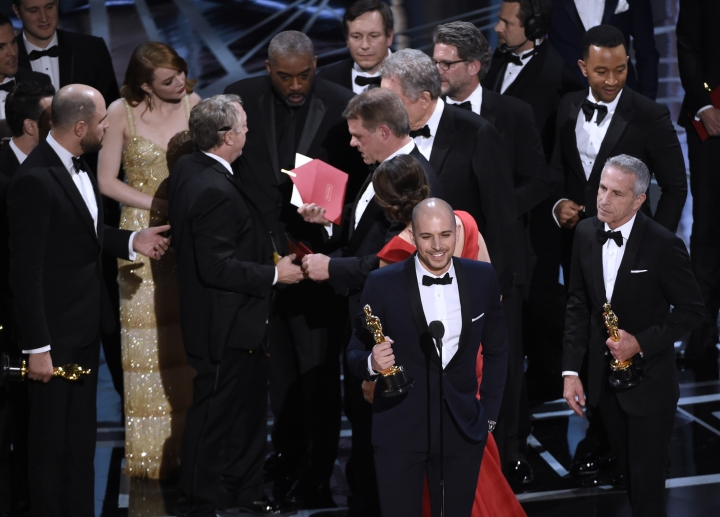 """Fred Berger, producer of """"La La Land,"""" foreground center, gives his acceptance speech as members of PricewaterhouseCoopers, Brian Cullinan, holding red envelope, and Martha L. Ruiz, in red dress, and a stage manager discuss the best picture announcement error among the cast at the Oscars on Sunday, Feb. 26, 2017, at the Dolby Theatre in Los Angeles. The actual winner of best picture went to """"Moonlight."""" (Photo by Chris Pizzello/Invision/AP)"""