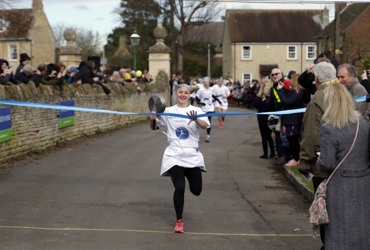 Kaia Larkas crosses the finish line to win the annual Shrove Tuesday trans-Atlantic pancake race in the town of Olney, in Buckinghamshire, England, Tuesday, Feb. 28, 2017. Every year women clad in aprons and head scarves from Olney and the city of Liberal, in Kansas, USA, run their respective legs of the race with a pancake in their pan. According to legend, the Olney race started in 1445 when a harried housewife arrived at church on Shrove Tuesday still clutching her frying pan with a pancake in it. Liberal challenged Olney to a friendly international competition in 1950 after seeing photos of the race in a magazine. This year however, the timing clock failed so there will be no race against Liberal. (AP Photo/Alastair Grant)