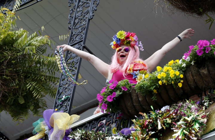 A woman encourages revelers below as she throws beads from a balcony, while the Society of Saint Anne Mardi Gras parade passes below in the French Quarter of New Orleans, Tuesday, Feb. 28, 2017. (AP Photo/Gerald Herbert)