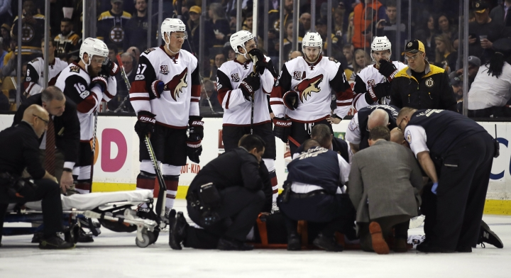Teammates watch as medical staffer attend to Arizona Coyotes center Alexander Burmistrov (91) following a hit by Boston Bruins defenseman Colin Miller during the second period of an NHL hockey game in Boston, Tuesday, Feb. 28, 2017. (AP Photo/Charles Krupa)