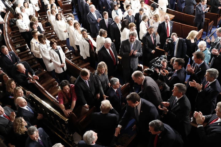 Women Democratic member of Congress, wearing white inn honor of women's suffrage, watch as President Donald Trump arrives on Capitol Hill in Washington, Tuesday, Feb. 28, 2017, to address a joint session of Congress. (AP Photo/Pablo Martinez Monsivais)