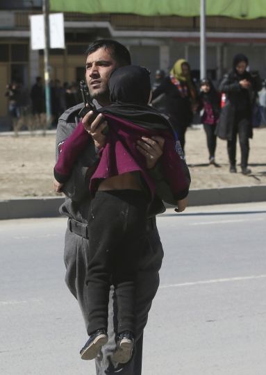 Afghan security police carries a girl after a suicide bombing in Kabul, Afghanistan, Wednesday, March 1, 2017. A pair of suicide bombings, both claimed by the Taliban, struck the Afghan capital, an Afghan official said. (AP Photo/Rahmat Gul)