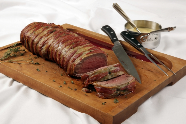 This Oct. 11, 2016 photo shows a Bacon-Wrapped Beef Tenderloin with Green Peppercorn and Thyme Sauce from a recipe by Elizabeth Karmel at the Institute of Culinary Education in New York. Beef tenderloin is much easier to prepare than prime rib, easier to carve and the leftovers are good cold. The only challenge with beef tenderloin is that it is lean, so it's best served rare. (AP Photo/Richard Drew)
