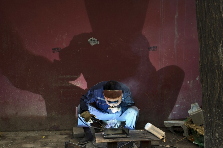FILE - In this July 17, 2016 file photo, a welder works at a construction site in Beijing. Chinese leaders are shrinking bloated industries including steel and coal in which supply exceeds demand, but Washington and Europe want them to move faster. A supply glut has led to a flood of low-cost Chinese exports that are hurting foreign competitors and threatening jobs abroad. (AP Photo/Ng Han Guan, File)