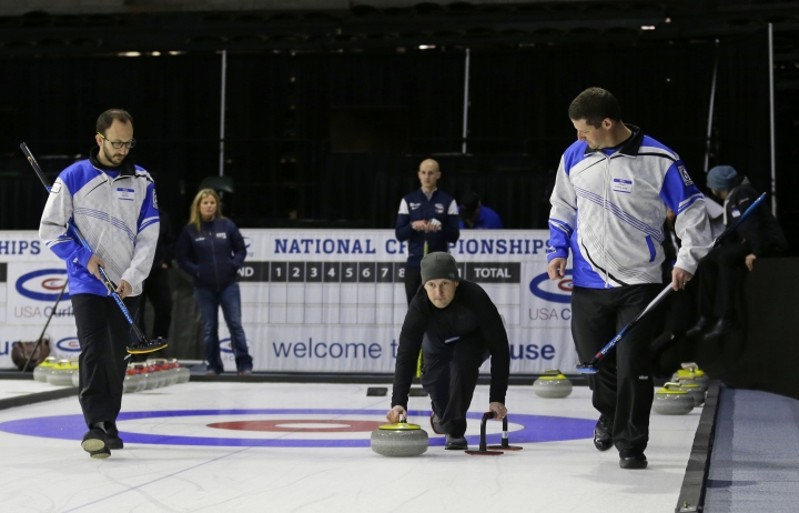 In this Wednesday, March 1, 2017 photo, Associated Press sportswriter Tim Booth, center, tries his hand at curling, during a media demonstration the day before the opening ceremonies of the USA Curling Nationals in Everett, Wash. Evan Jaffe, left, and Josh Chetwynd, right, of Team Sobering, prepare to sweep. (AP Photo/Ted S. Warren)