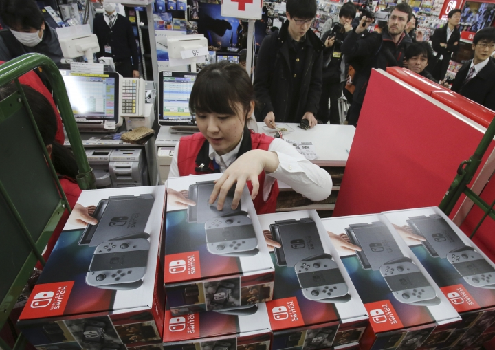 "Employee of the electronics retailer Bic Camera sells Nintendo's newest computer game ""Switch"" at a retail store in central Tokyo. Friday, March 3, 2017. (AP Photo/Koji Sasahara)"