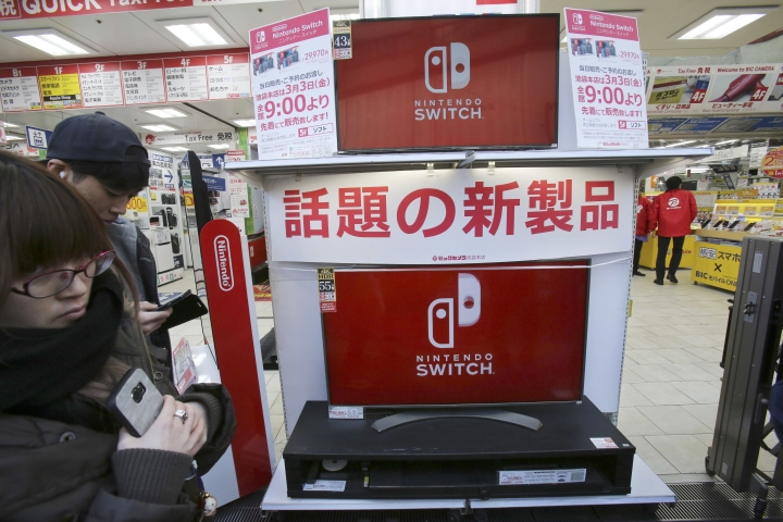 "Shoppers wait at outside retail store Bic Camera to buy Nintendo's newest computer game ""Switch"" in central Tokyo, Friday, March 3, 2017. (AP Photo/Koji Sasahara)"