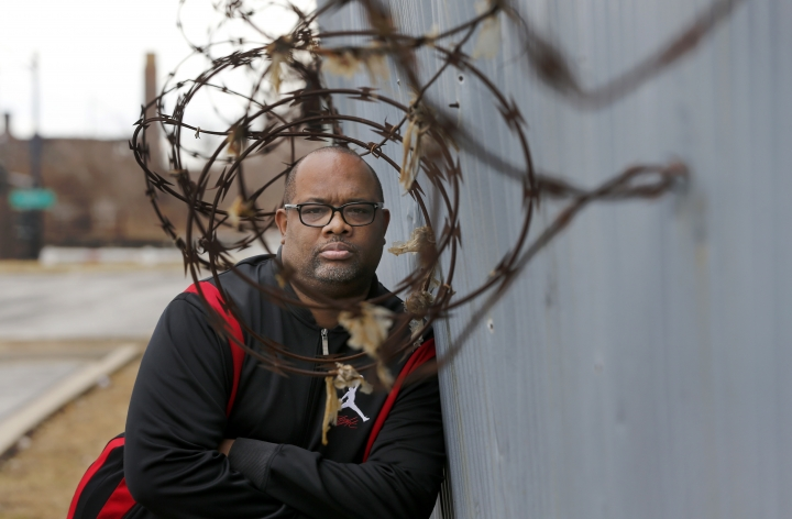 In this Tuesday, Feb. 21, 2017, photo, Pastor Corey Brooks of the New Beginnings Church poses for a portrait on a under maintained security wall that hugs the sprawling Norfolk Southern train yard and his church on Chicago's South Side. When street-gang thieves slipped into a Norfolk Southern rail yard on Chicago's South Side and ripped locks off one train, they likely expected to see merchandise like toys or tennis shoes. What they beheld instead was a gangster's jackpot: box after box of brand new guns. (AP Photo/Charles Rex Arbogast)