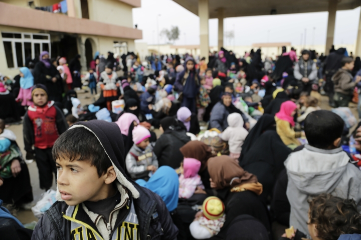Civilians who fled clashes between Iraqi forces and Islamic State group fighters in Mosul are gathered at an old gas station south of the city Friday, Marc 3, 2017. Thousands of civilians continue to flee the city each day as the humanitarian situation for the hundreds of thousands trapped along with IS fighters in western Mosul continues to deteriorate. (AP Photo/Susannah George)