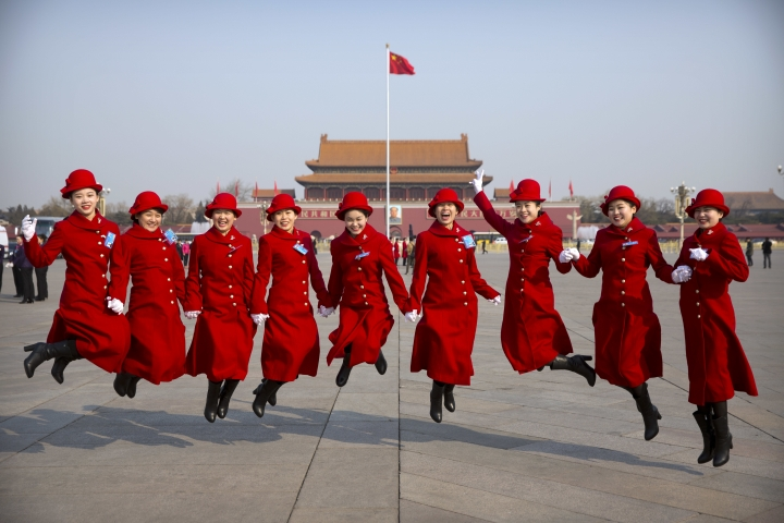 Bus ushers leap as they pose for a group photo at Tiananmen Square during a plenary session of the National People's Congress in Beijing, Saturday, March 4, 2017. China will raise its defense budget by about 7 percent this year, a government spokeswoman said Saturday, continuing a trend of lowered growth amid a slowing economy. (AP Photo/Mark Schiefelbein)