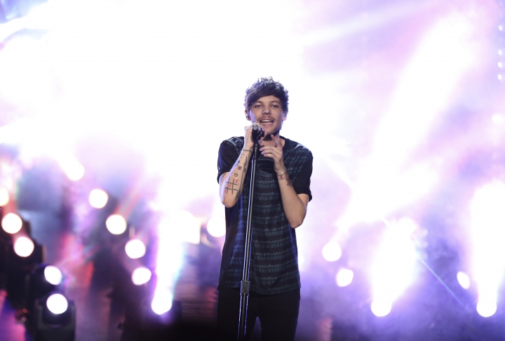 """FILE - In this Nov. 22, 2015 file photo, Louis Tomlinson of One Direction performs at the American Music Awards at the Microsoft Theater on in Los Angeles. Tomlinson has been arrested for allegedly attacking a photographer at Los Angeles International Airport, an incident the singer's lawyer described as """"provoked"""" by paparazzi. The incident happened Friday, March 3, 2017, after Tomlinson, arriving on a flight with his girlfriend, Eleanor Calder, asked a photographer to stop filming (Photo by Matt Sayles/Invision/AP)"""