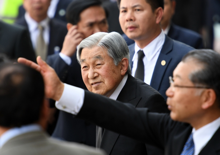 Japan's Emperor Akihito, center, is flanked by security men on his arrive at the Phu Bai airport in the central city of Hue, Vietnam as he prepares to depart for Thailand, ending his six-day long royal visit in the southeast communist country Sunday, March 5, 2017. (Hoang Dinh Nam/Pool Photo via AP)