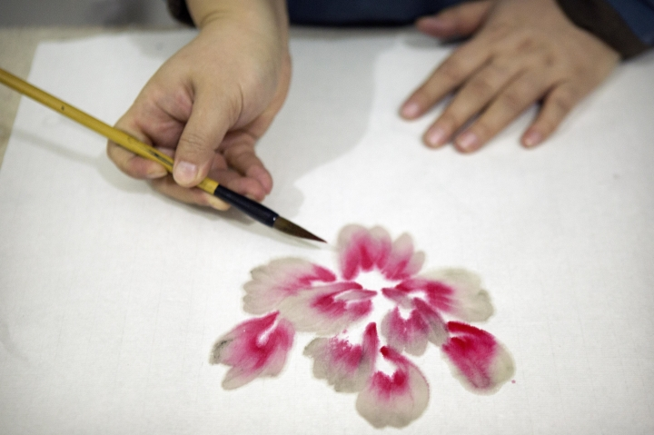 In this Monday, Feb. 27, 2017 photo, Ye Haiyan paints a watercolor painting in her studio on the outskirts of Beijing. Ye has resorted to advocating for the rights of sex workers and people with HIV/AIDS through painting after her blogs have been closed down, she has moved from city to city following harassment from authorities, and police told her to leave her latest home ahead of the annual meeting of China's ceremonial parliament that opened Sunday. (AP Photo/Mark Schiefelbein)