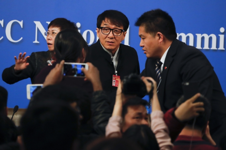 Journalists take pictures of Hong Kong movie star Jackie Chan, delegate to the Chinese People's Political Consultative Conference, center, after a press conference on the sideline of the CPPCC at the media center in Beijing, Tuesday, March 7, 2017. Jackie Chan says letting more Hollywood movies into the Chinese market would put pressure on Chinese filmmakers to boost the quality of their domestic output. (AP Photo/Andy Wong)