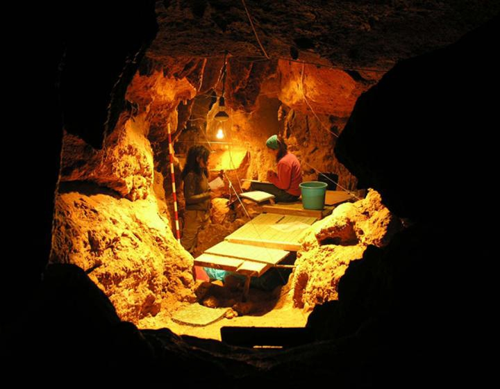 In this photo provided by Antonio Rosas, Paleoanthropology Group MNCN-CSIC, shows work in the Tunnel of Bones cave, where 12 Neanderthal specimens dating around 49,000 years ago have been recovered. Scientists got a sneak peek into the kitchen and medicine cabinets of three Neanderthals by examining the DNA of the stuff stuck on and between their teeth. What they found smashes a common meaty misconception of the caveman diet and hints that one sickly Neanderthal had found what may be primitive versions of penicillin and aspirin to help him with his pain. (Antonio Rosas/Paleoanthropology Group MNCN-CSIC via AP)