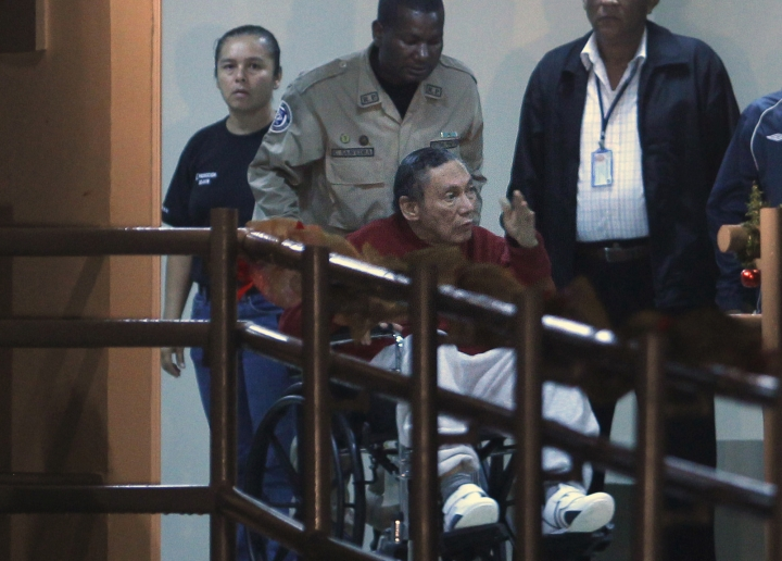 FILE - In this Dec. 11, 2011 file photo, Panama's ex-dictator Manuel Noriega is pushed in a wheelchair by a police officer inside El Renacer prison on the outskirts of Panama City. Noriega, 83, is in critical condition after undergoing two brain surgeries Tuesday, March 7, 2017. Noriega underwent the first procedure Tuesday morning to remove a benign tumor from his brain. But after that surgery, doctors discovered a hemorrhage that forced them to go back in that afternoon, his daughters and lawyer said. (AP Photo/Esteban Felix, File)