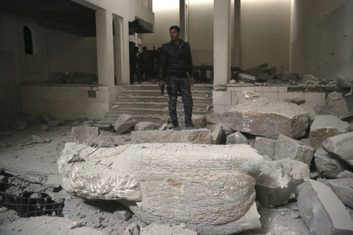 Iraqi federal police inspect the inside of Mosul's heavily damaged museum. Most of the artifacts inside the building appeared to be completely destroyed. The basement level that was the museum's library had been burned. The floors were covered in the ashes of ancient manuscripts, in western Mosul, Iraq, Wednesday, March 8, 2017. (AP Photo/Khalid Mohammed)